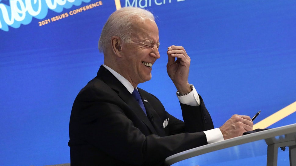 U.S. President Joe Biden laughs during a virtual meeting with the House Democratic Caucus in the Eisenhower Executive Office Building in Washington, D.C., U.S., on Wednesday, March 3, 2021. Biden has agreed to moderate Democrats' demands to narrow eligibility for stimulus checks, but rejected a push to trim extra unemployment benefits, as he tries to win support for his $1.9 trillion pandemic-relief bill, according to a Democratic aide.