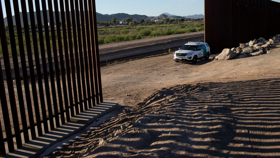 YUMA, ARIZONA - APRIL 30: United States Border Patrol agents guard a gap in the new border wall along the Colorado River where families from Central and South America have been crossing into the United States from Mexico to ask for asylum, April 30, 2021 outside of Yuma, Arizona. (Photo by Andrew Lichtenstein/Corbis via Getty Images)