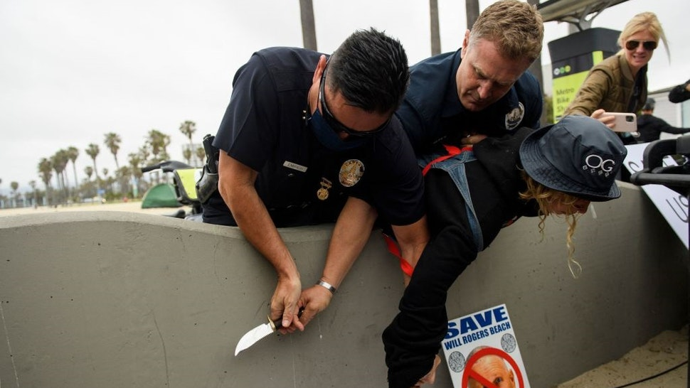 """Los Angeles Police Department (LAPD) offices wrestle a knife away from a person experiencing homelessness as they were detained during an event with Los Angeles City Council Member and mayoral candidate Joe Buscaino announcing his """"Plan For A Safer Los Angeles"""" at Venice Beach on June 7, 2021 in Los Angeles, California."""