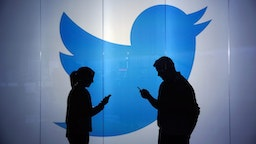People are seen as silhouettes as they check mobile devices whilst standing against an illuminated wall bearing Twitter Inc.'s logo in this arranged photograph in London, U.K., on Tuesday, Jan. 5, 2016.