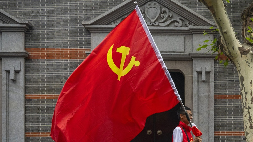 """SHANGHAI, CHINA - JUNE 17: A man carries the hammer and sickle flag outside of the Memorial of the First National Congress of the Communist Party of China, on June 17, 2021 in Shanghai, China. The memorial, built where the first congress of the party was started before being interrupted by authorities in 1921, is considered, together with Nanhu Red Boat in Jiaxing, the physical birthplace of the CPC and it is one of the key sites of the so called """"Red Tourism""""."""