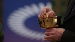 """15 May 2021, Hessen, Frankfurt/Main: A member of the church congregation holds a wafer in his hand in front of the logo of the ÖKT during a service with communion in the Catholic Cathedral of St. Bartholomew. The service is being held as part of the 3rd Ecumenical Church Day. Four services will be held simultaneously in the city, all under the motto """"Celebrating the Eucharist in an ecumenically sensitive way"""". Photo: Sebastian Gollnow/dpa"""