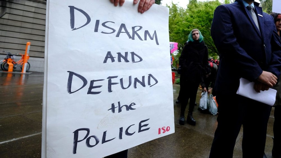 """PORTLAND, USA - APRIL 11: A protester holds a sign reading """"Disarm And Defund The Police"""" during a protest against fatal police shootings in Portland, Oregon, United States on April 11, 2018. John Andrew Elifritz, 48, was fatally shot by police after he reportedly fled from a stolen car and burst into a homeless shelter at the start of an alcoholics anonymous meeting last Saturday."""