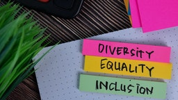 """""""Diversity, Equality and Inclusion"""" written on a sticky note isolated on Office Desk."""