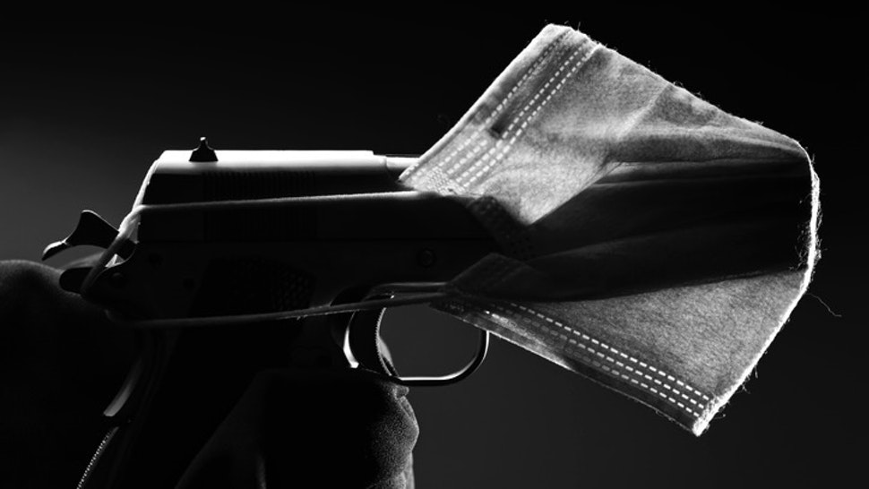 Health weaponized - stock photo A side shot of a face mask covering a gun representing how the current pandemic us being used to further some ambitions Images By Tenyo via Getty Images