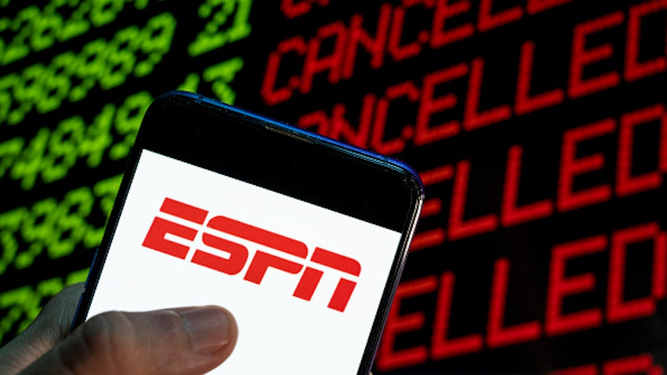 CHINA - 2021/04/24: In this photo illustration the American sports television channel ESPN logo is seen on an Android mobile device with the word cancelled on a computer screen.