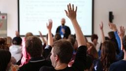 Students Raising Hands During Seminar