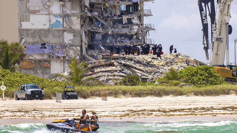 SURFSIDE, FLORIDA - JUNE 26: Members of the South Florida Urban Search and Rescue team look for possible survivors in the partially collapsed 12-story Champlain Towers South condo building on June 26, 2021 in Surfside, Florida. Over 150 people are being reported as missing as search-and-rescue efforts continue with rescue crews from across Miami-Dade and Broward counties.