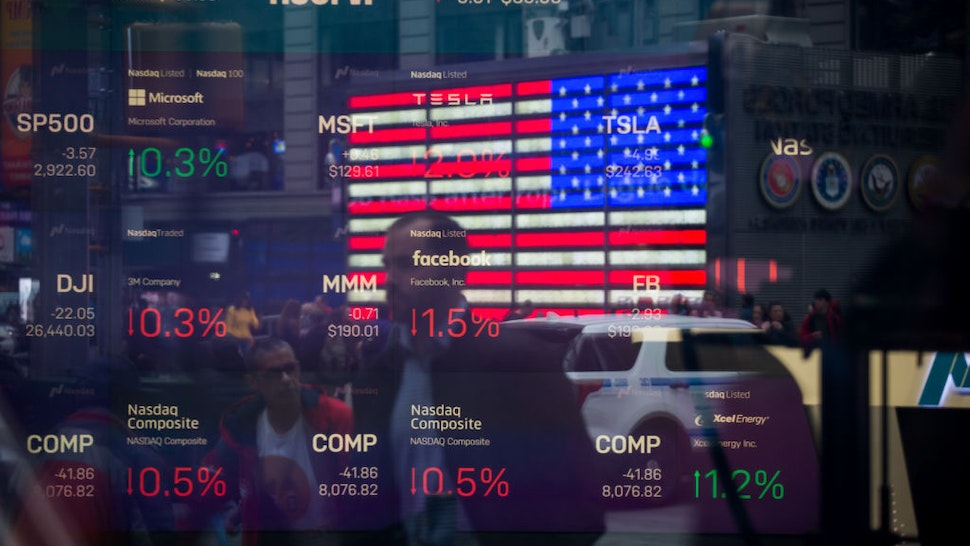 Monitors display stock market information as pedestrians are reflected in a window at the Nasdaq MarketSite in the Times Square area of New York, U.S., on Friday, April 26, 2019. U.S. stocks edged higher on better-than-forecast earnings while Treasury yields fell after data signaled tepid inflation in the first quarter. Photographer: Michael Nagle/Bloomberg via Getty Images