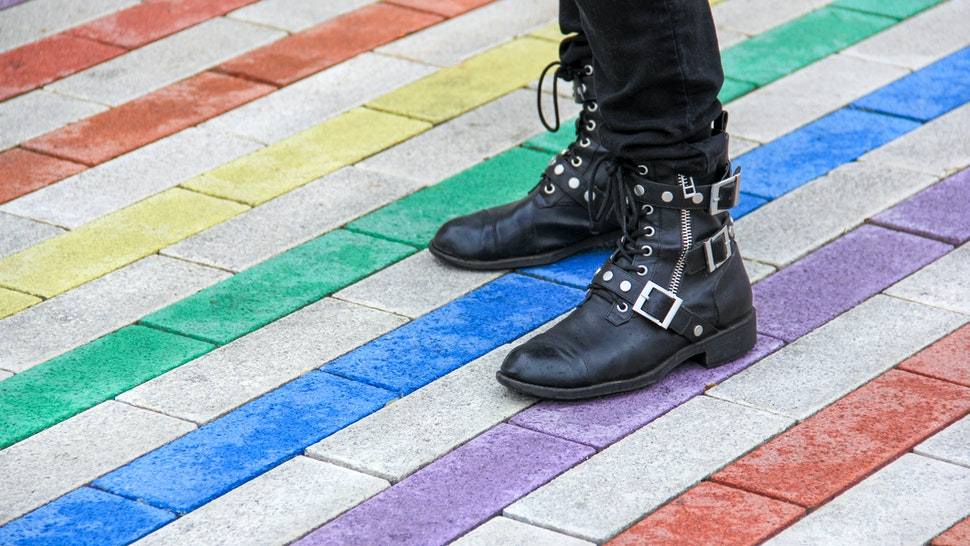 Person standing on colorful rainbow sidewalk - stock photo