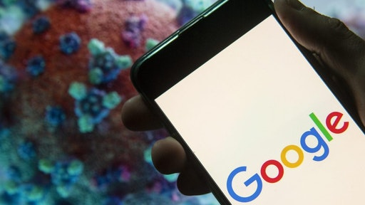 CHINA - 2020/03/23: In this photo illustration the American multinational technology company and search engine Google logo seen displayed on a smartphone with a computer model of the COVID-19 coronavirus on the background.