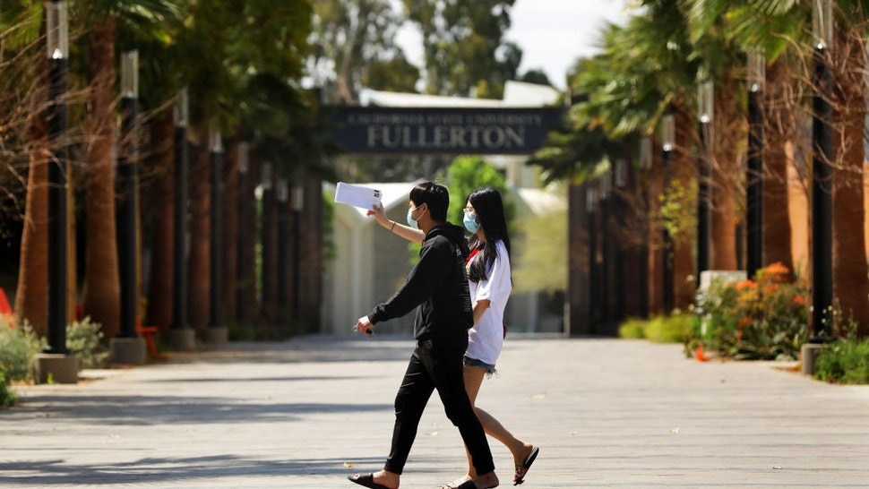 Cal State University Fullerton student Linh Trinh, 21, right, and her boyfriend Tan Nguyen, 21, walk around a deserted CSUF campus on Tuesday, April 21, 2020.