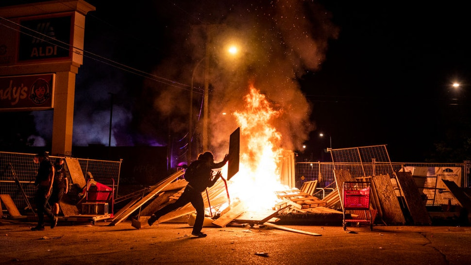 A protester throws a piece of wood on a fire in the street just north of the 3rd Police Precinct on May 27, 2020 in Minneapolis, Minnesota.