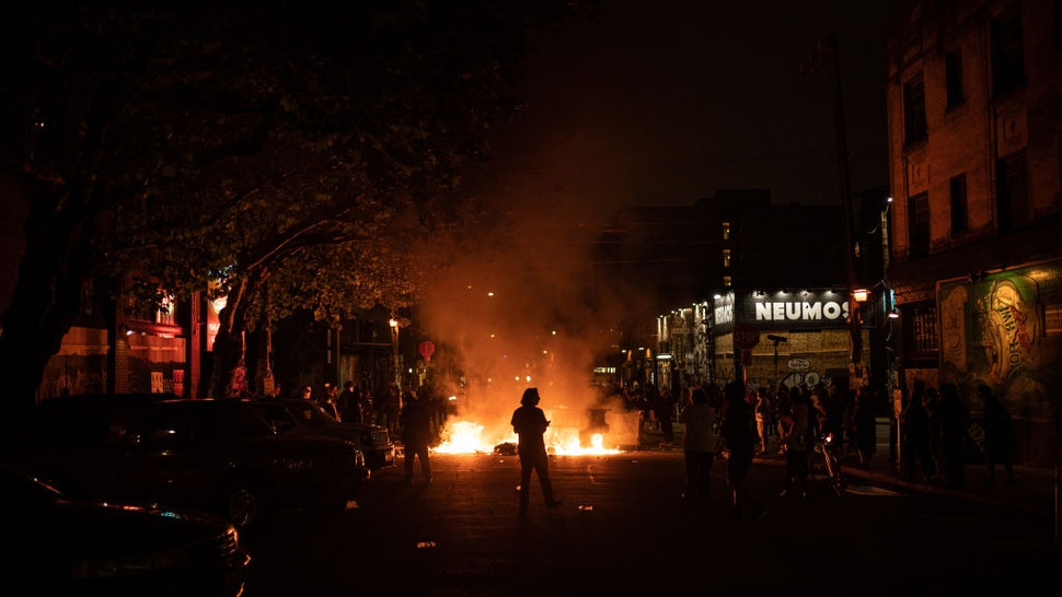 A demonstrator watches a fire burn in the street after clashing with law enforcement near the Seattle Police Departments East Precinct shortly after midnight on June 8, 2020 in Seattle, Washington.
