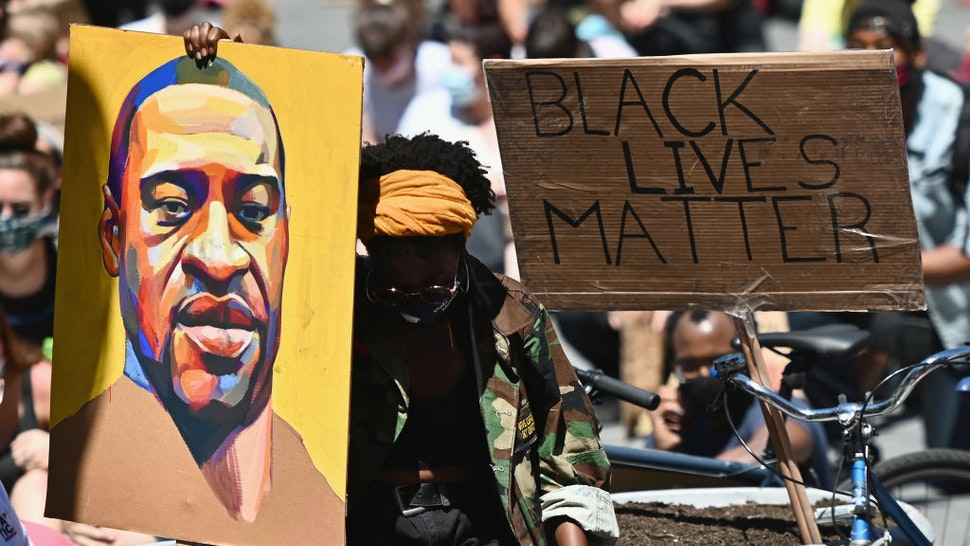 """TOPSHOT - Protesters hold up signs during a """"Black Lives Matter"""" protest in front of Borough Hall on June 8, 2020 in New York City. - On May 25, 2020, Floyd, a 46-year-old black man suspected of passing a counterfeit $20 bill, died in Minneapolis after Derek Chauvin, a white police officer, pressed his knee to Floyd's neck for almost nine minutes. (Photo by Angela Weiss / AFP) (Photo by ANGELA WEISS/AFP via Getty Images)"""