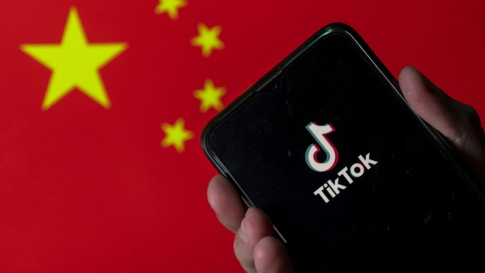 CHINA - 2020/08/11: In this photo illustration the Chinese video-sharing social networking service company, TikTok logo is seen on an Android mobile device with People's Republic of China flag in the background.
