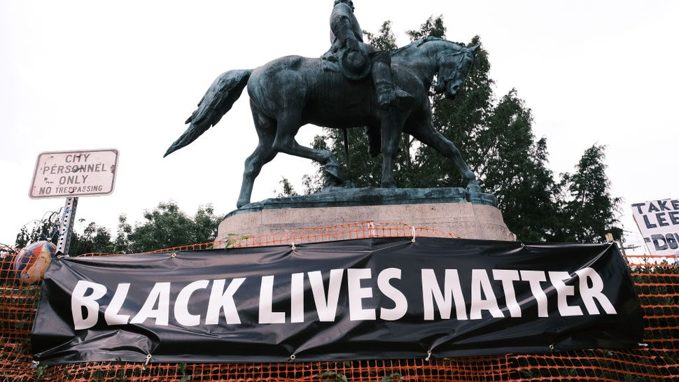 """CHARLOTTESVILLE, VA - AUGUST 12: The statue of Robert E Lee with a banner that reads """"Black Lives Matter"""" during the """"Reclaim the Park"""" gathering at Emancipation Park on August 12, 2020 in Charlottesville, Virginia. Community members in Charlottesville collaborated with Congregate Cville and other Charlottesville organizations to put together the """"Reclaim the Park"""" gathering to mark the third anniversary of a far-right rally on August 12, 2017."""