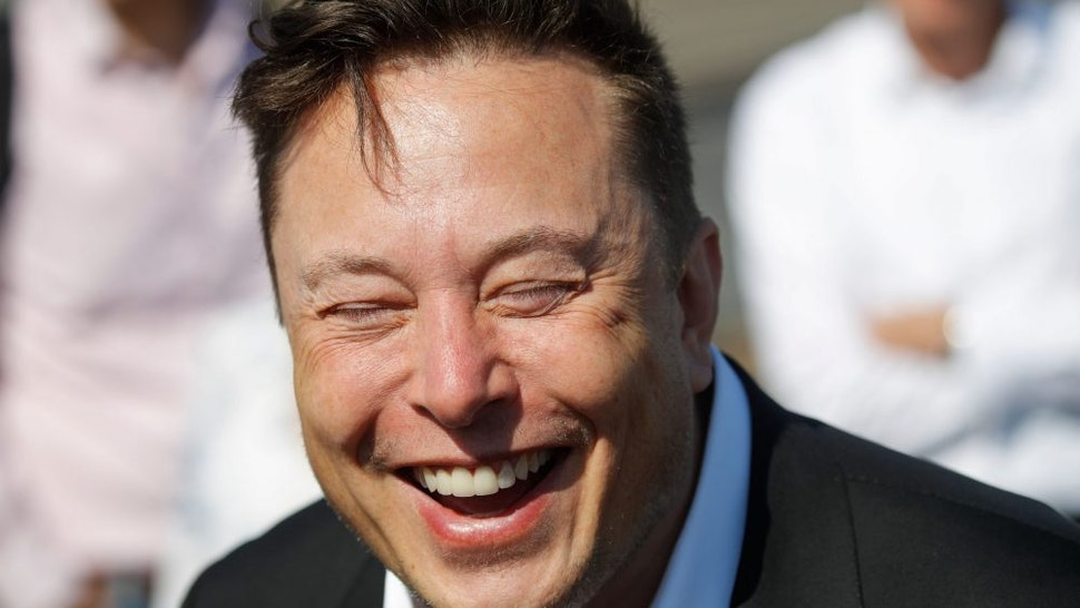 """Tesla CEO Elon Musk laughs as he talks to media as he arrives to visit the construction site of the future US electric car giant Tesla, on September 03, 2020 in Gruenheide near Berlin. - Tesla builds a compound at the site in Gruenheide in Brandenburg for its first European """"Gigafactory"""" near Berlin."""