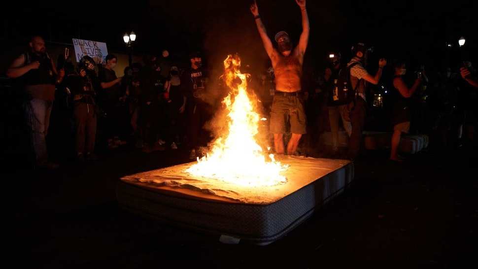 A protestor dances as mattresses are set on fire in front of the North Precinct Police building in Portland, Oregon on September 6, 2020.
