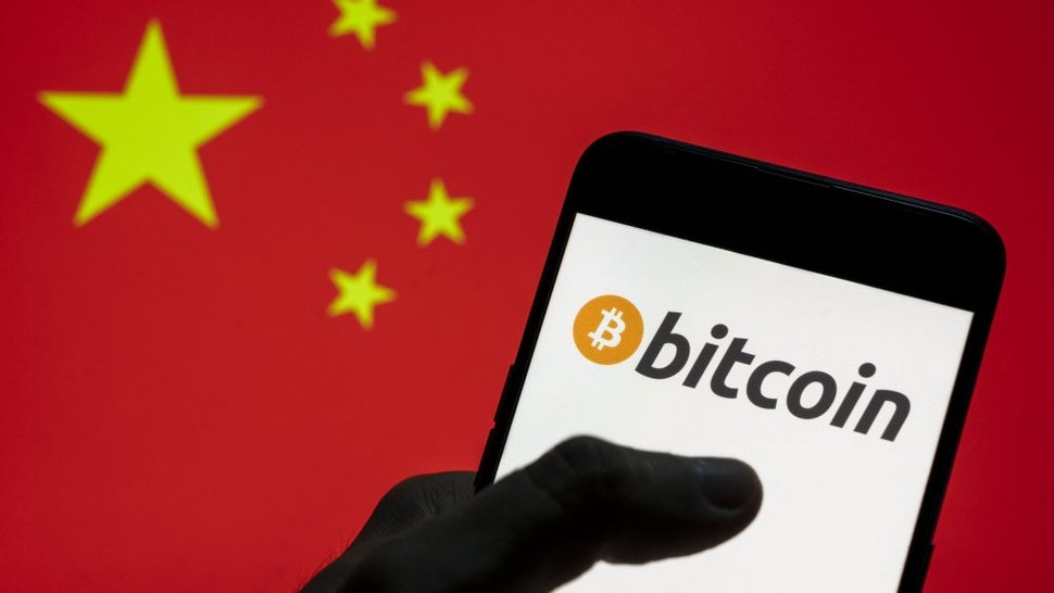 CHINA - 2021/03/28: In this photo illustration the Cryptocurrency electronic cash Bitcoin logo seen on an Android mobile device with People's Republic of China flag in the background.
