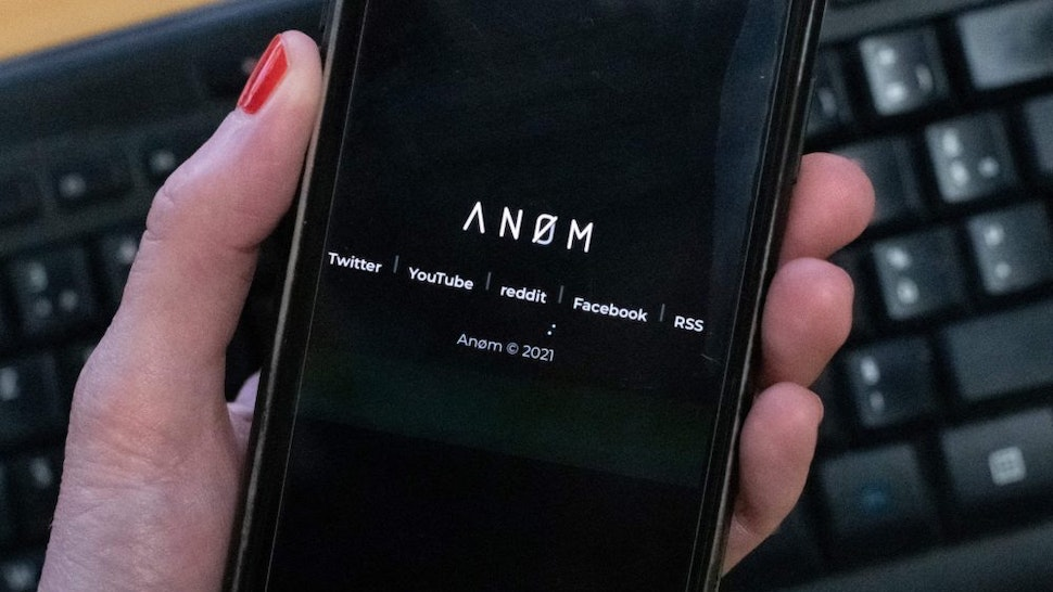 An illustration picture shows the ANoM logo displayed on the screen of an smartphone on june 8, 2021 in Paris. - Some 250 people were arrested in Sweden and Finland in the global sting on organised crime, authorities said on June 8, 2021, using phones planted by the US FBI, law enforcement officers were able to read the messages of global underworld figures in around 100 countries as they plotted drug deals, arms transfers and gangland hits on the compromised ANOM devices.