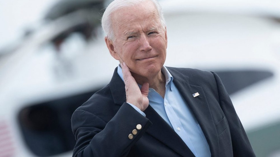 US President Joe Biden wipes his neck after a cicada landed on him while boarding Air Force One at Andrews Air Force Base, before departing for the UK and Europe to attend a series of summits on June 9, 2021, in Maryland. - President Biden departed Washington early Wednesday on the first foreign trip of his presidency, launching an intense series of summits with G7, European and NATO partners before a tense face-to-face with Russia's Vladimir Putin.