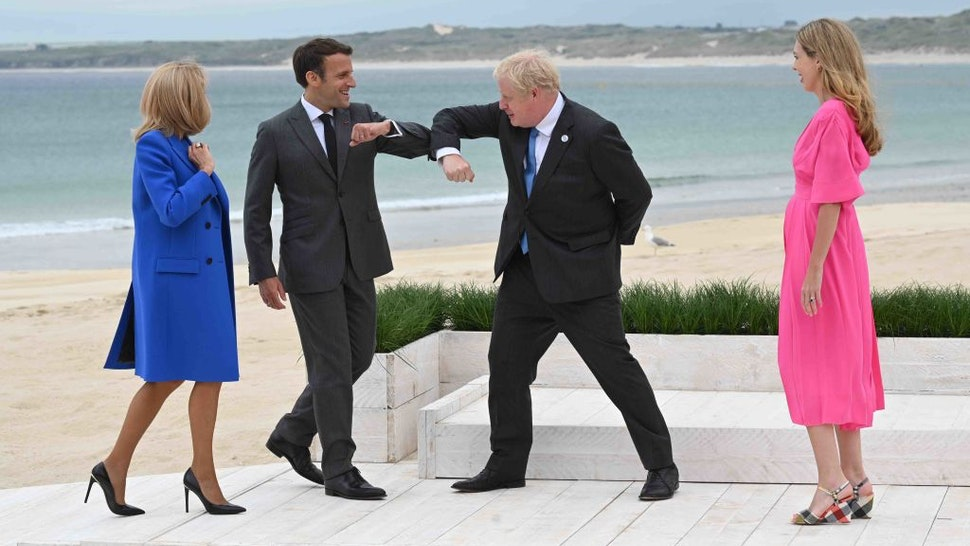 CARBIS BAY, CORNWALL - JUNE 11: Prime Minister of United Kingdom, Boris Johnson, greets President of France, Emmanuel Macron with an elbow bump as Carrie Johnson and Brigitte Macron, look on, during the Leaders official welcome and family photo during the G7 Summit In Carbis Bay, on June 11, 2021 in Carbis Bay, Cornwall. UK Prime Minister, Boris Johnson, hosts leaders from the USA, Japan, Germany, France, Italy and Canada at the G7 Summit. This year the UK has invited India, South Africa, and South Korea to attend the Leaders' Summit as guest countries as well as the EU.