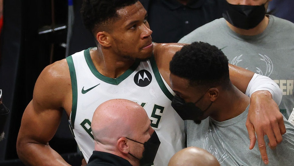 ATLANTA, GEORGIA - JUNE 29: Giannis Antetokounmpo #34 of the Milwaukee Bucks is helped off the court after being injured on a play against the Atlanta Hawks during the second half in Game Four of the Eastern Conference Finals at State Farm Arena on June 29, 2021 in Atlanta, Georgia. NOTE TO USER: User expressly acknowledges and agrees that, by downloading and or using this photograph, User is consenting to the terms and conditions of the Getty Images License Agreement. (Photo by Kevin C. Cox/Getty Images)