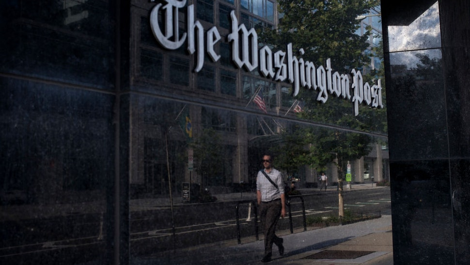 A man walks past The Washington Post on August 5, 2013 in Washington, DC after it was announced that Amazon.com founder and CEO Jeff Bezos had agreed to purchase the Post for USD 250 million.