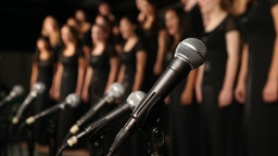 Shot of microphones with choir in the background - stock photo