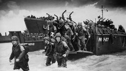 6th June 1944: Reinforcements disembarking from a landing barge at Normandy during the Allied Invasion of France on D-Day. (Photo by Hulton Archive/Getty Images)
