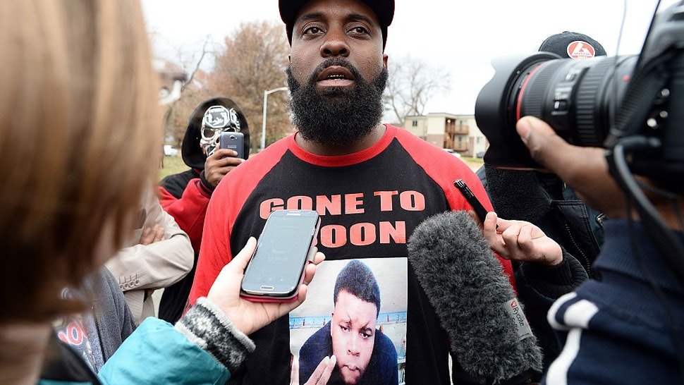 Michael Brown Sr. (C), the father of 18-year-old Michael Brown who was shot dead by a police officer, speaks to journalists as he distributes turkeys for Thanksgiving where his son was killed in Ferguson, Missouri, on November 22, 2014.