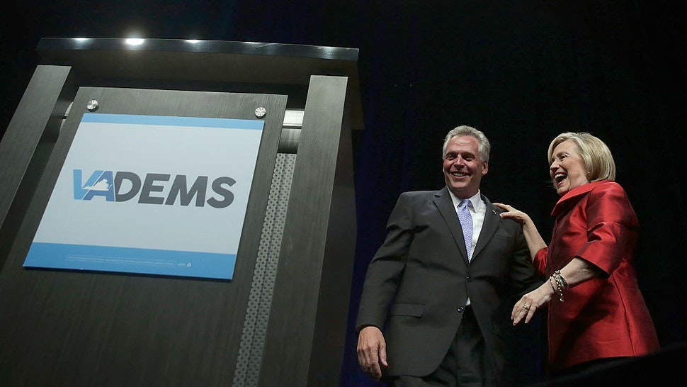Democratic U.S. presidential hopeful and former U.S. Secretary of the State Hillary Clinton and Virginia Governor Terry McAuliffe share a moment during the Democratic Party of Virginia Jefferson-Jackson dinner June 26, 2015 at George Mason University's Patriot Center in Fairfax, Virginia.