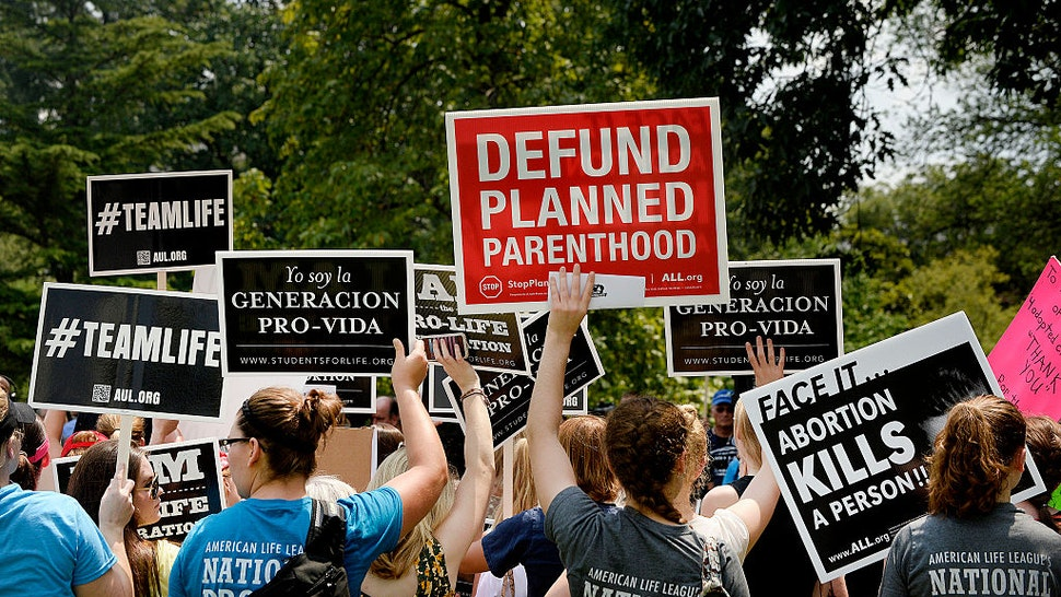 WASHINGTON, DC - JULY 28: Anti-abortion activists hold a rally opposing federal funding for Planned Parenthood in front of the U.S. Capitol on July 28, 2015 in Washington, DC. Sen. Rand Paul (R-KY) announced a Senate deal to vote on legislation to defund Planned Parenthood before the Senate goes into recess in August.