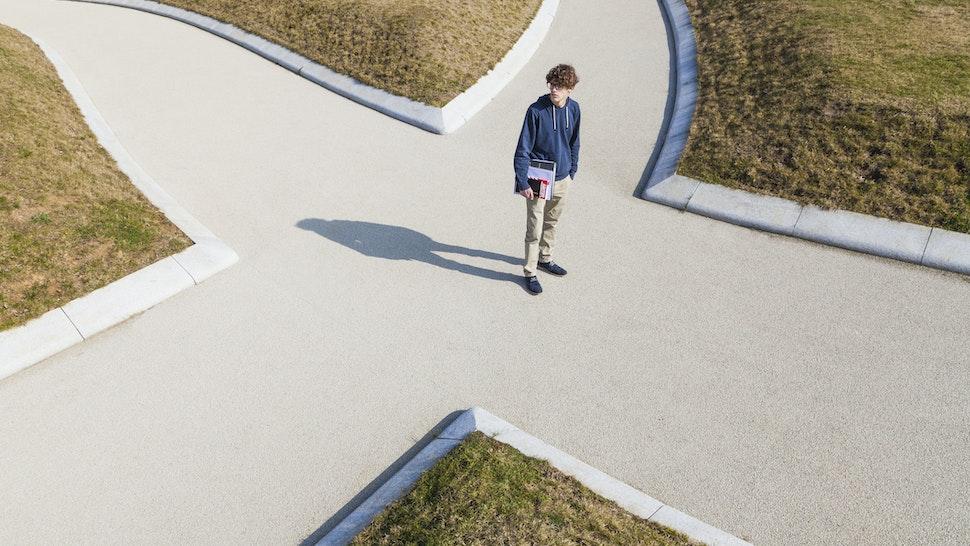 Teenage boy standing at crossing - stock photo