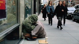 A group of women walk past a homeless woman begging for money along a city sidewalk. (Photo by © Viviane Moos/CORBIS/Corbis via Getty Images)