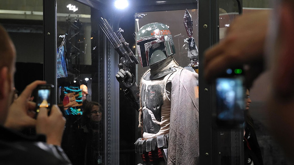 People take pictures of a Boba Fett model before the world premiere of 'Star Wars: A Musical Journey' at the O2 Arena in east London, on April 10, 2009.. The show features an extensive selection of composer John Williams' scores from all six Star Wars movies in a two-hour musical event which includes scenes from the movies, live narration and, at the O2, the 86 piece Royal Philharmonic Orchestra and Choir. AFP PHOTO/Leon Neal (Photo credit should read Leon Neal/AFP via Getty Images)