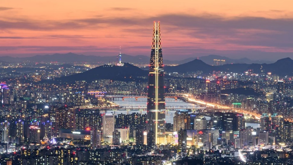TOPSHOT - This photo taken on May 19, 2018 shows a general view of the Lotte tower (front C) and Namsan tower (rear C) amid the Seoul city skyline and Han river during sunset. (Photo by Ed JONES / AFP) (Photo credit should read ED JONES/AFP via Getty Images)