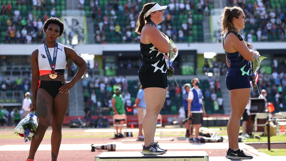 EUGENE, OREGON - JUNE 26: Gwendolyn Berry (L), third place, turns away from U.S. flag during the U.S. National Anthem as DeAnna Price (C), first place, and Brooke Andersen, second place, also stand on the podium after the Women's Hammer Throw final on day nine of the 2020 U.S. Olympic Track & Field Team Trials at Hayward Field on June 26, 2021 in Eugene, Oregon. In 2019, the USOPC reprimanded Berry after her demonstration on the podium at the Lima Pan-American Games.