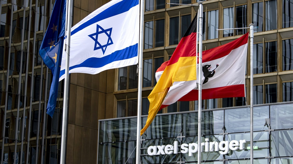 16 May 2021, Berlin: The Israeli flag, which was raised on Sunday morning, flies in front of the Axel Springer building. In addition, the (l-r) European, German and Berlin flags can be seen.