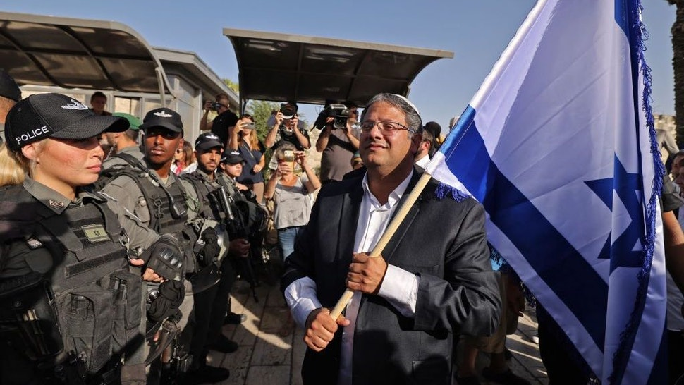 """Itamar Ben-Gvir, member of Israel's Knesset (parliament) and head of the one-man far right """"Jewish Power"""" (Otzma Yehudit) party, waves an Israeli flag as he attempts to march to Damascus Gate in east Jerusalem, on June 10, 2021. (Photo by EMMANUEL DUNAND / AFP) (Photo by EMMANUEL DUNAND/AFP via Getty Images)"""