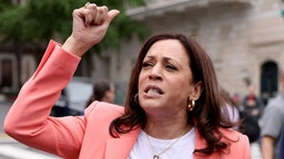 WASHINGTON, DC - JUNE 12: U.S. Vice President Kamala Harris speaks to marchers, as her husband Doug Emhoff looks on, during the Capitol Pride Parade on June 12, 2021 in Washington, DC. Capital Pride returned to Washington DC, after being canceled last year due to the Covid-19 pandemic.