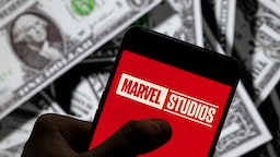 CHINA - 2021/04/23: In this photo illustration, a Marvel Studios logo seen displayed on a smartphone with USD (United States dollar) currency in the background.