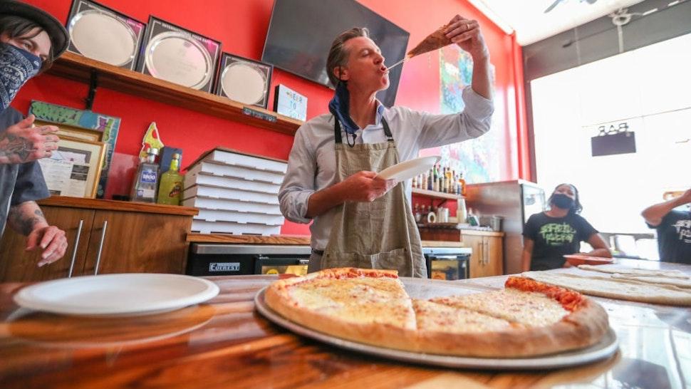 OAKLAND, CA - JUNE 17: Graffiti Pizza executive chef Matt Molina, left, looks on as California Governor Gavin Newsom tries a slice of pizza during a visit to Graffiti Pizza in Oakland, Calif., on Thursday, June 17, 2021.