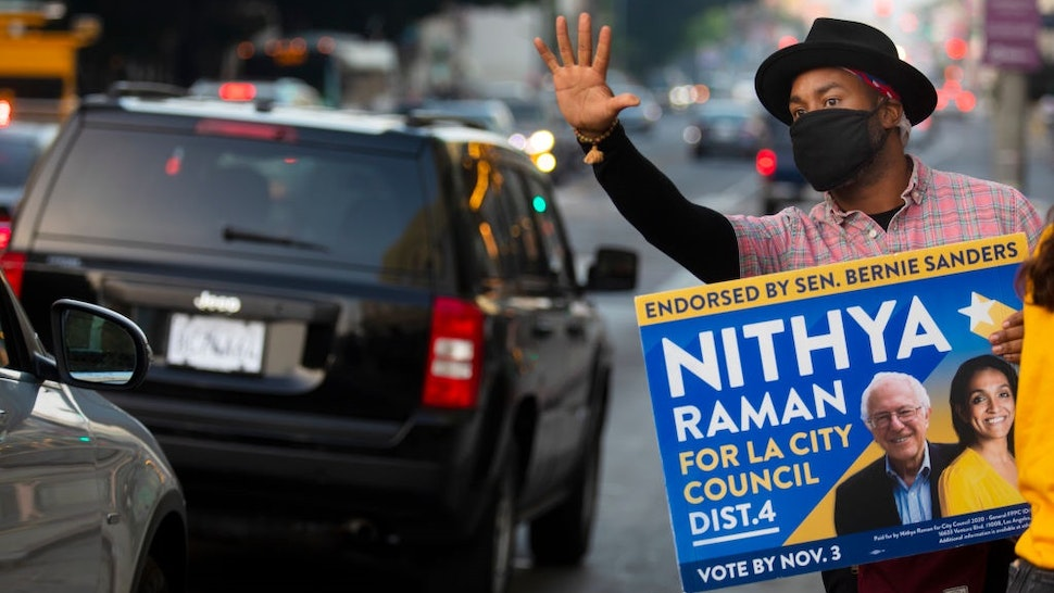 LOS ANGELES, CA - NOVEMBER 03: As the sun begins to set Matthew Gaston, 37, of Los Angeles, holds up a vote sign for Nithya Raman for LA City Council down the street from a voting center inside The Wiltern on election day on Tuesday, Nov. 3, 2020 in Los Angeles, CA.