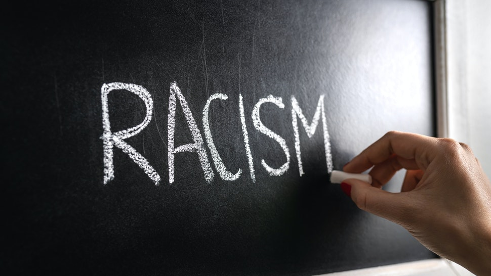 Hand writing the word racism on blackboard.