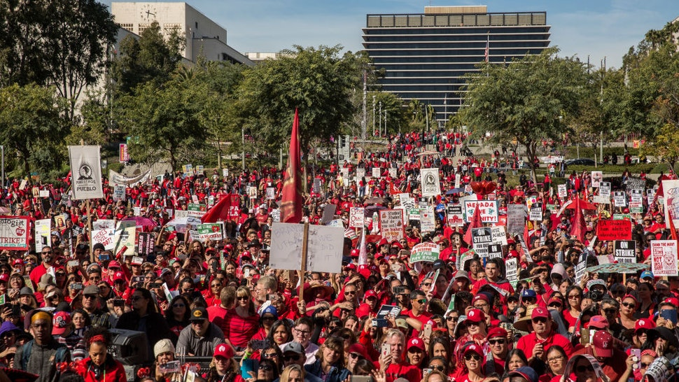 LOS ANGELES, CA - JANUARY 22: Educators, parents, students, and supporters of the Los Angeles teachers strike wave and cheer in Grand Park on January 22, 2019 in downtown Los Angeles, California.Thousands of striking teachers cheered for victory at the rally after it was announced that a tentative deal between the United Teachers of Los Angeles union and the Los Angeles Unified School District heavily favored educators' demands including a cap on rising class sizes, funding for school nurses, and a significant pay increase.