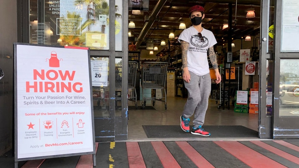 LARKSPUR, CALIFORNIA - APRIL 02: A customer walks by a now hiring sign at a BevMo store on April 02, 2021 in Larkspur, California.