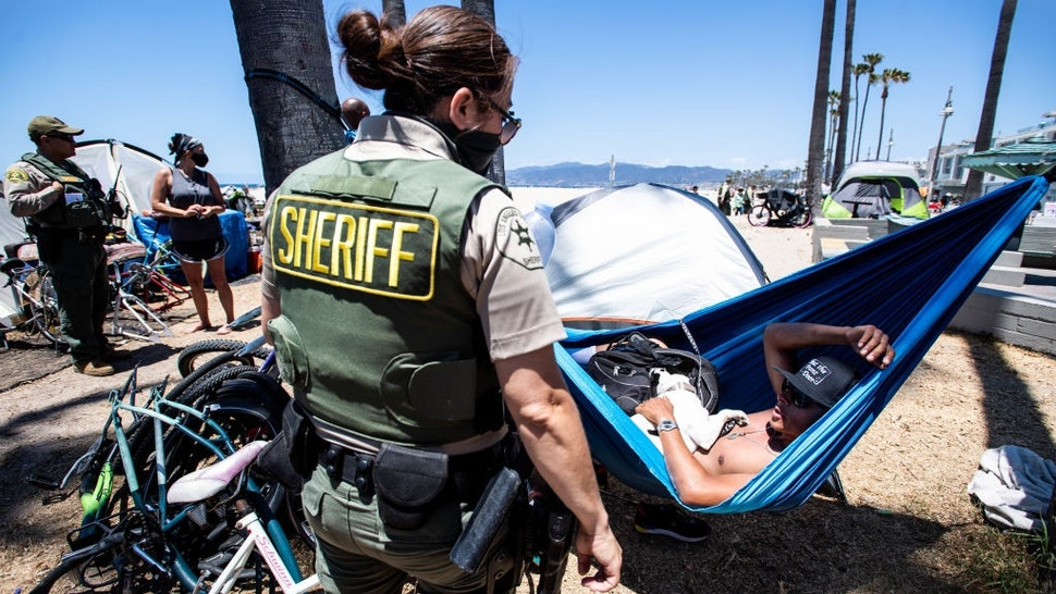 VENICE, CA - JUNE 08:Sheriff deputy Matson, of the Homeless Outreach Services Teams, encourages René Reyes, 28, on Tuesday, June 8, 2021 to leave the homeless encampment along the Venice Boardwalk where he has been living for the past three months after a divorce.