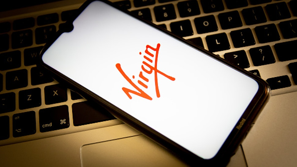 GREECE - 2021/04/23: In this photo illustration, a Virgin logo seen displayed on a smartphone screen with a computer keyboard in the background.